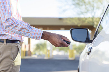 Midsection of man using remote car door opener