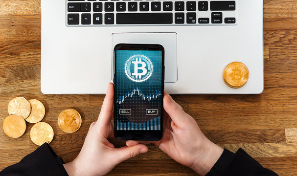 Human using smartphone app to buy or sell bitcoins. Bankntotes, laptop and gold coins of BTC on table.