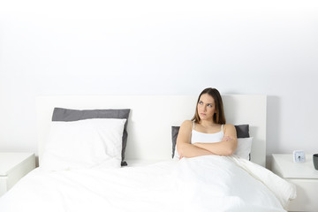 Angry woman sitting on the bed looking at side