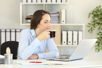 Businesswoman enjoying a cup of coffee at office