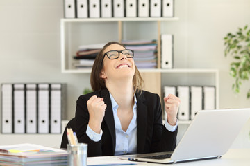 Excited businesswoman celebrating success at office