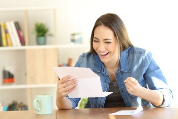 Excited woman reading good news in a letter