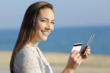 Girl holding a credit card and phone looking at camera