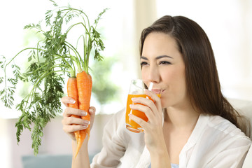 Woman drinking carrot juice at home