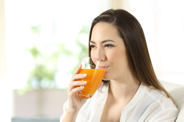 Woman drinking orange juice in a glass