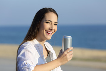 Woman holding a refreshment can looking at camera