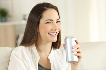 Woman holding a refreshment can looking at you