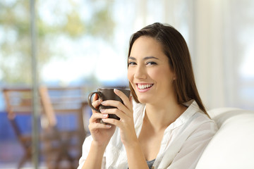 Woman looking at camera holding a coffee mug