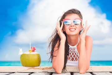 long haired woman in bikini and sunglasses with fresh coconut cocktail relaxing on tropical beach