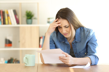 Worried woman reading bad news in a letter