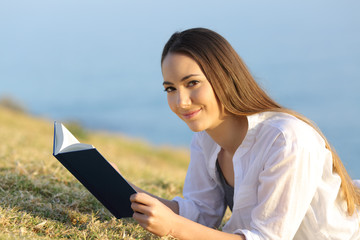 Woman reading a book looking at camera on the grass