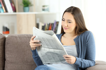 Woman reading a newspaper sitting on a couch