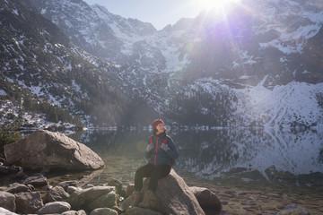 Female hiker sitting on rock at lakeside