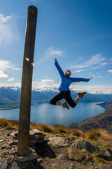 A woman jumping up in the air on the summit of a mountain with a lake in the background.