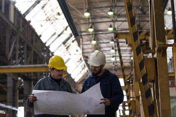 Technician discussing blueprint with his colleague