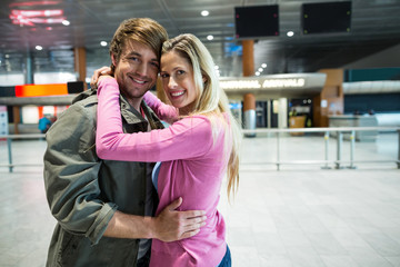 Portrait of smiling couple embracing each other in waiting area