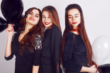 Crazy party time of three beautiful stylish women in elegant evening casual black dress celebrating , having fun, dancing on white background. Best friends girls with black and white balloon .