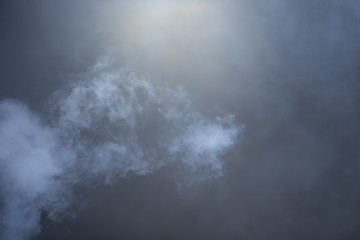 Blue-grey cloud of smoke emerges from bottom left over a hazy black background