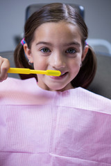 Young patient brushing her teeth at dentists clinic
