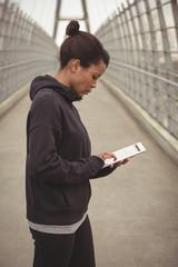 Woman using digital tablet on bridge