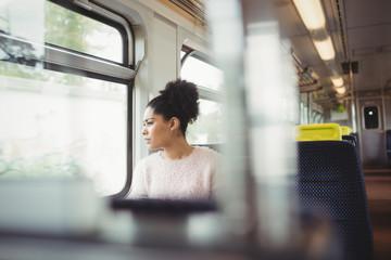 Thoughtful smart woman looking through window in train