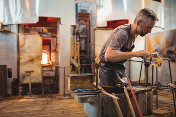 Glassblower shaping a molten glass