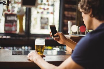 Man using mobile phone with glass of beer in hand