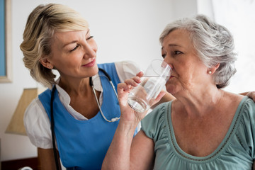 Nurse giving medicaments to a senior woman