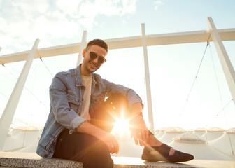 fashion guy sitting at sunset posing in sun glasses
