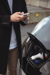 Mid section of man using mobile phone while charging electric car