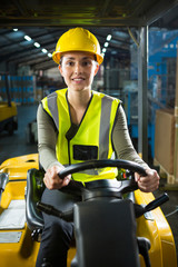 Beautiful female worker driving forklift in warehouse