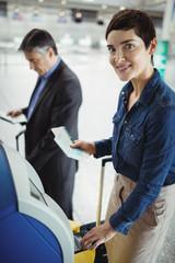 Businesswoman using self service check-in machine