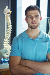 Portrait of male physiotherapist standing with arms crossed