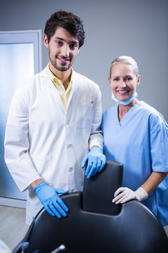 Dentist and dental assistant smiling at camera
