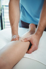 Physiotherapist giving physical therapy to the leg of a female patient