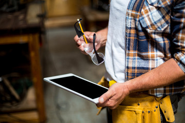 Carpenter using digital tablet in workshop