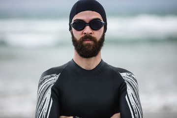 Athlete in wet suit standing with his arms crossed