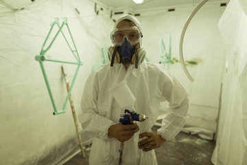 Portrait of painter holding paint spray gun while wearing gas mask