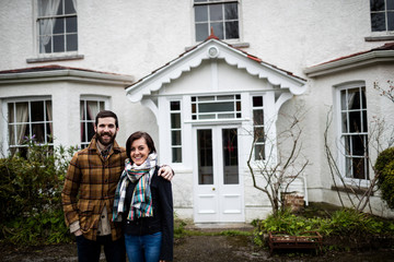 Portrait of couple standing near a new house
