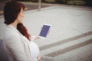 Pregnant businesswoman holding digital tablet