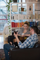 Man playing guitar while woman sitting beside him in living room