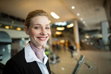 Portrait of smiling airline check-in attendant at counter