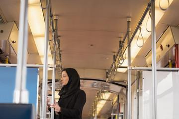 Woman in hijab travelling in train