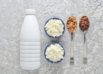 Healthy, dietary food. Morning breakfast. A bottle of yogurt, bowls with cottage cheese, spoons with walnuts and raisins on a gray concrete table. Top view. Flat lay food..