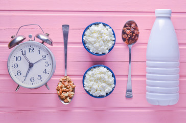 Healthy, dietary food. Morning breakfast. A bottle of yogurt, bowls with cottage cheese, spoons with walnuts and raisins, alarm clock on a pink wooden table. Top view. Flat lay food..