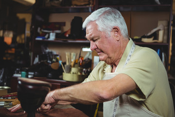 Shoemaker cutting a piece of leather