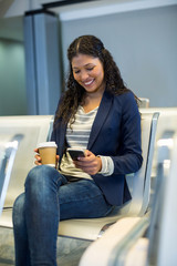 Female commuter with coffee cup using mobile phone in waiting area