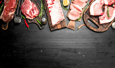 Different types of raw pork meat and beef with herb and spices.