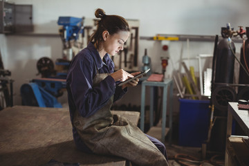 Female welder using digital tablet