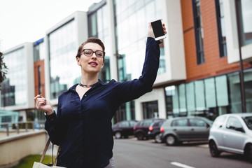 Businesswoman holding mobile phone on road